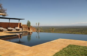 Relax around the infinity pool between safari activities